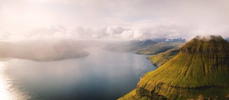 Foggy mountain peaks and clouds covering sea and mountains. Panoramical view from famous place - Sornfelli on Streymoy island, Faroe islands, Denmark. Landscape photography