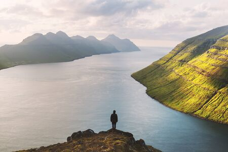 Tourist on famous viewpoint on Klakkur peak near Klaksvik city on Kalsoy island, Faroe Islands, Denmark. Landscape photography