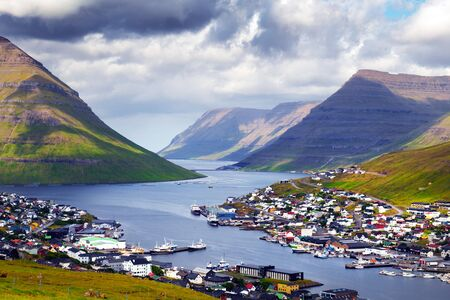 Breathtaking cityscape of Klaksvik town with fjord and cloudy mountains, Bordoy island, Faroe islands, Denmark. Landscape photography