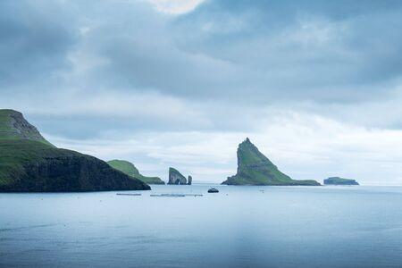 Dramatic view on Drangarnir and Tindholmur sea stacks in Atlantic ocean, Faroe Islands. Landscape photography