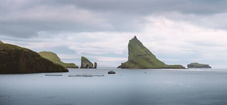 Dramatic panoramical view on Drangarnir and Tindholmur sea stacks in Atlantic ocean, Faroe Islands. Landscape photography 版權商用圖片