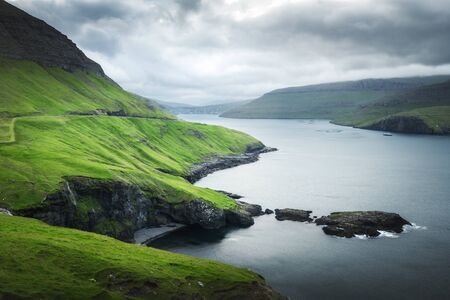 Dramatic view of green hills of Vagar island and Sorvagur town on background. Faroe islands, Denmark. Landscape photography