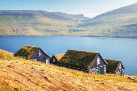 Picturesque view of tradicional faroese grass-covered houses in the village Bour during autumn. Vagar island, Faroe Islands, Denmark.