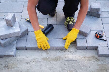 El maestro de guantes amarillos coloca adoquines en capas. Camino de ladrillos de jardín pavimentado por un trabajador profesional de la pavimentadora. Colocación de losas de hormigón gris en el patio de la casa sobre una base de arena.