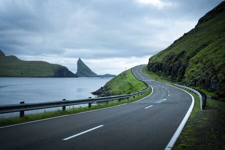Dramatic evening view of the road and the Drangarnir and Tindholmur rocks in the background on the island of Vagar, Faroe Islands, Denmark