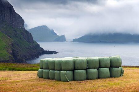 Rural scene with farm field and hay stacks on the Gasadalur village, Vagar island, Faroe Islands. Drangarnir and Tindholmur on background