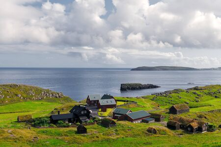 Summer view of small village with typical faroese turf-top houses on outskirts of Torshavn city, capital of Faroe Islands, Streymoy island, Denmark. Landscape photography
