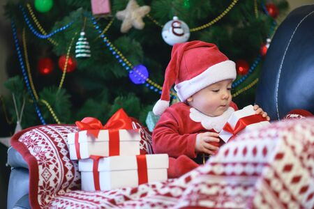 Baby boy in Santas clothes holding Christmas present gift box in front of Christmas tree 版權商用圖片