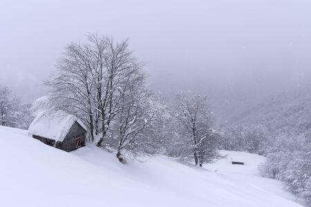 Fantástico paisaje invernal con casa de madera en montañas nevadas. Concepto de vacaciones de Navidad Foto de archivo