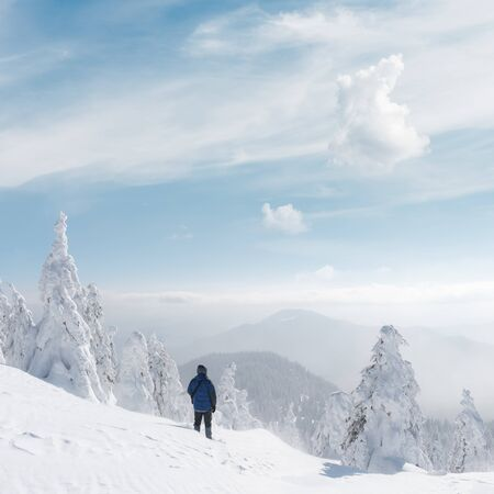 Alone tourist with a backpack in the high mountains in winter time. Travel concept 版權商用圖片
