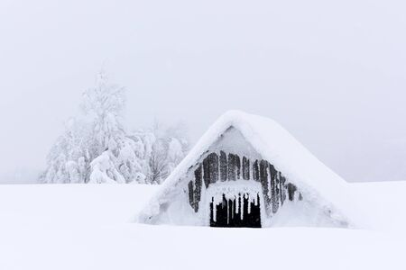 Fantastic winter landscape with old wooden house in snowy mountains. Christmas holiday concept