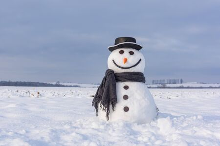 Funny snowman in stylish hat and black scarf on snowy field.