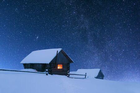 Fantastische Nachtlandschaft, die durch die Milchstraße glüht. Dramatische winterliche Szene mit schneebedecktem Haus mit Licht im Fenster. Karpaten, Ukraine, Europa. Standard-Bild