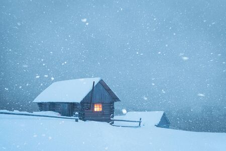 Fantastic winter landscape with wooden house in snowstorm in snowy mountains. Christmas holiday and winter vacations concept