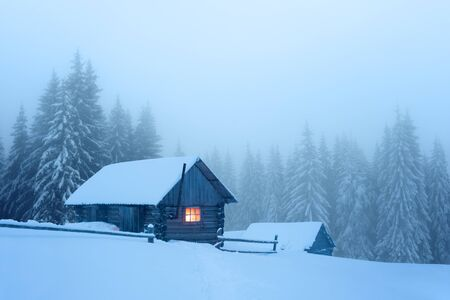 Fantastic winter landscape with wooden house in snowy and foggy mountains forest. Christmas holiday and winter vacations concept