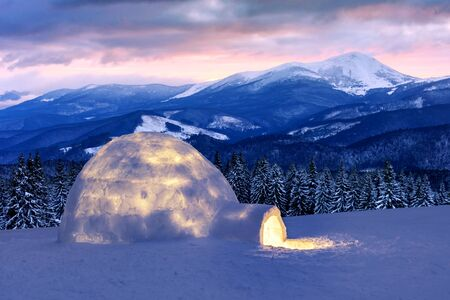 Real snow igloo house in the winter mountains. Snow-covered firs and mountain peaks on the background. Foggy forest with snowy spruce