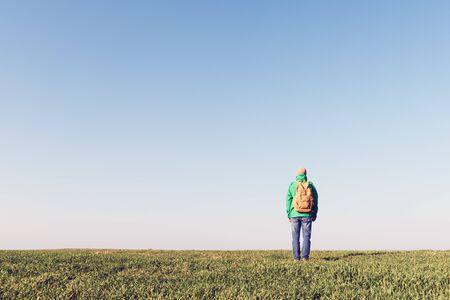 Tourist with backpack alone on summer field. Travel concept Reklamní fotografie