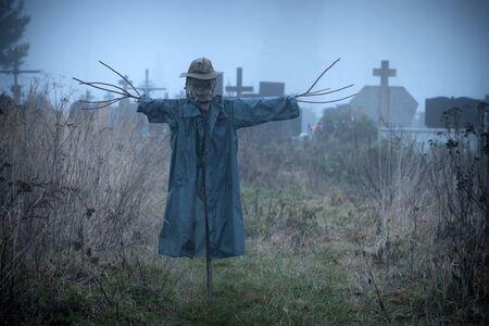 Terrible scarecrow in dark cloak and dirty hat stands alone on a cemetery background. Halloween concept