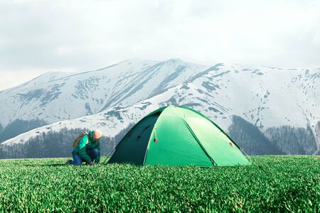 Tourist pitch a tent on green meadow in spring mountains. Amazing highland. Landscape photography 版權商用圖片