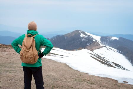 Tourist in green jacket with backpack in spring snowy mountains. Travel concept. Landscape photography