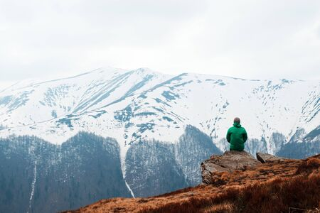 Man in green jacket sitting on rock in spring mountains. Travel concept. Landscape photography