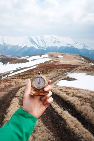 Retro compass in man hand in high mountains. Travel concept. Landscape photography