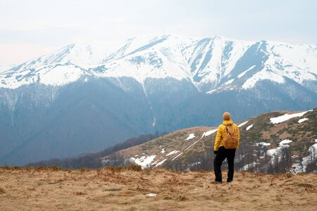 Man in yellow jacket with backpack in spring snowy mountains. Travel concept. Landscape photography