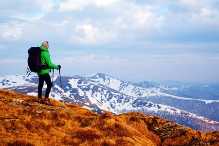 Amazing landscape with snowy mountains range and hiker with black backpack on a foreground 版權商用圖片