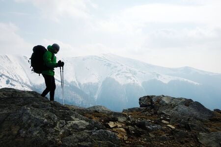 Hiker with backpack silhouette on snowy mountains range background