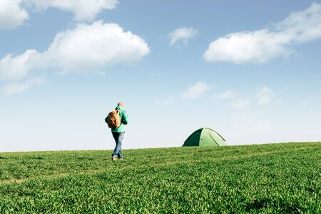 Tourist with backpack going to his tent on summer field. Blue cloudy sky. Travel concept