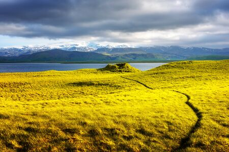Gorgeous Iceland landscape with green grass field, blue lake and snow-capped mountains in the background. Iceland, Europe