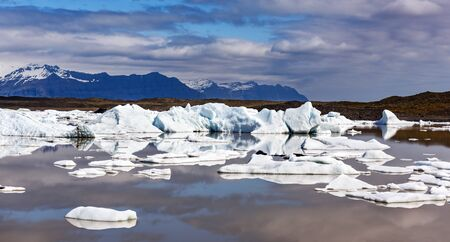 Panoramical view of Fjallsarlon glacial lagoon. Icebergs and mountains in Vatnajokull National Park, southeast Iceland, Europe. Landscape photography