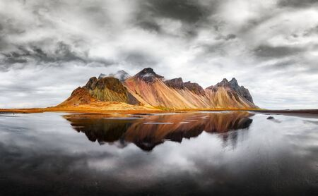 Incredible landscape of the famous Stokksnes mountains on Vestrahorn cape. Reflection in the clear water on the epic skies background, Iceland