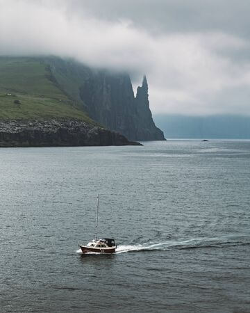 Gorgeous faroese landscape with famous Witches Finger cliffs and dramatic cloudy sky. Vagar island, Faroe Islands, Denmark.