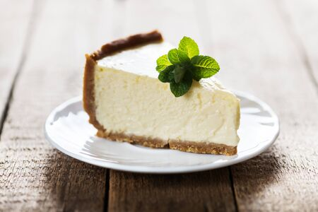 Slice of classic New York cheesecake with a sprig of mint on a plate on a wooden table. The concept of bakery and sweet cakes desserts