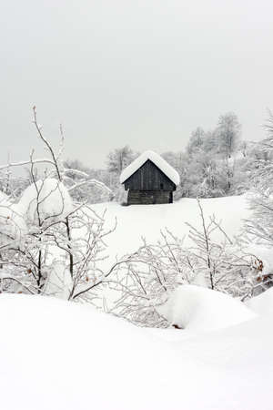 Minimalistic winter landscape with wooden house in snowy mountains. Cloudy weater, landscape photography