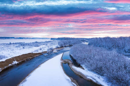 Flight through majestic river, frozen forest and frosty winter fields at sunrise time. Landscape photography