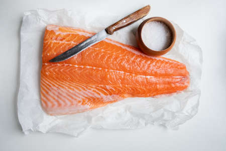 Fillet of salmon fish on wooden table with knife and salt. Food photography Standard-Bild
