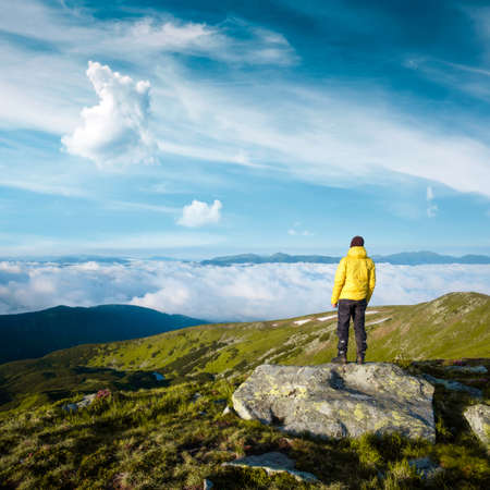 Alone tourist in yellow jacket stay on rock on high mountains. Landscape photography