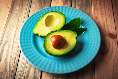 Fresh avocado fruit on a blue plate on wooden table. The concept of healthy eating. Food photography
