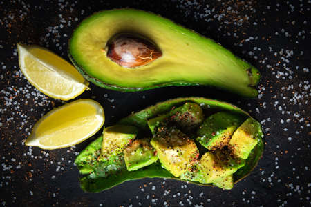 Fresh avocado fruit on a black rustic board. The concept of healthy eating. Food photography