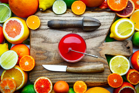 Mix of different citrus fruits and glass of juice with wooden board, squeezer and knife closeup. Healthy diet vitamin concept. Food photography Standard-Bild