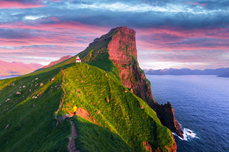 Kallur lighthouse on green hills of Kalsoy island on sunset time, Faroe islands, Denmark. Landscape photography
