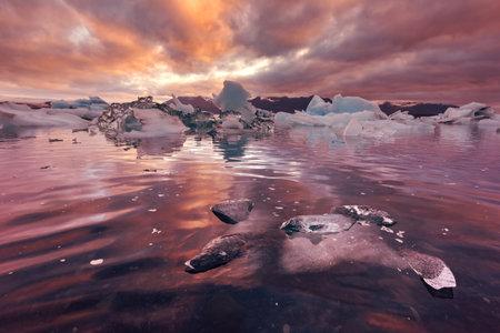 Orange sunset and icebergs in Jokulsarlon glacial lagoon. Vatnajokull National Park, southeast Iceland, Europe. Landscape photography