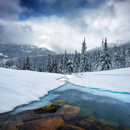 Fantastic winter landscape with frozen river and snowy trees in foggy mountains. Carpathian mountains, Ukraine, Europe. Christmas holiday concept Standard-Bild