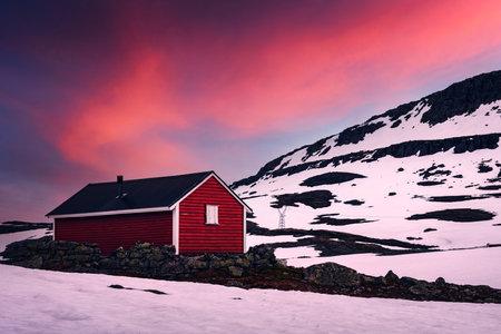 Typical norwegian red wooden house near famous Aurlandsvegen (Bjorgavegen) mountain road in Aurland, Norway in sunset time. Landscape photography Standard-Bild