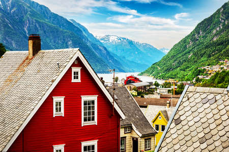 Typical norwegian houses near fjord and snowy mountains. Norway, Europe. Landscape photography Standard-Bild