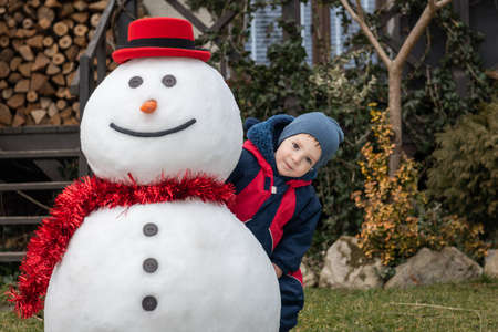 Funny snowman in stylish red hat and small boy on lawn near house. Merry Christmass and happy New Year