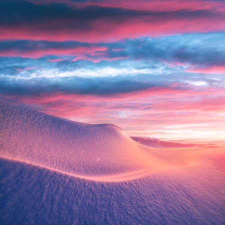 Fantastic winter landscape in snowy mountains glowing by morning sunlight. Dramatic wintry scene with frozen snowy hills at sunrise. Christmas holiday background Standard-Bild