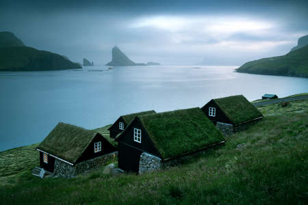 Picturesque view of tradicional faroese grass-covered houses in the village Bour. Drangarnir and Tindholmur sea stacks on background. Vagar island, Faroe Islands, Denmark. Landscape photography